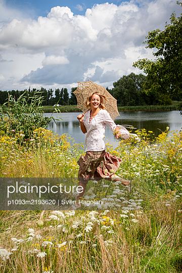 Blonde Frau läuft durch eine Wiese mit blühenden Blumen - p1093m2193620 von Sven Hagolani
