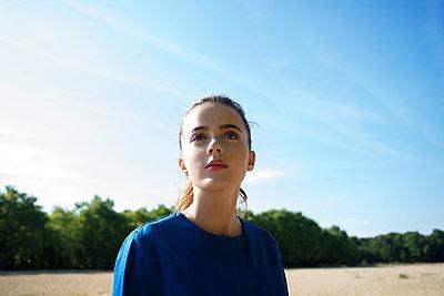 Girl in blue coat in the field - p1096m1051342 by Rajkumar Singh