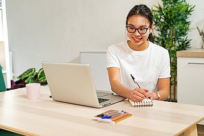 Smiling woman writing in notepad while sitting with laptop at home - p300m2266166 by Giorgio Fochesato