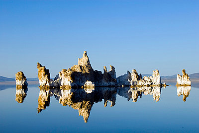 Large tufa formations are illuminated and reflected in afternoon light in Mono Lake, CA - p3437201f by Rachid Dahnoun