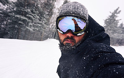 Self-Portrait of snowboarder riding down trail  - p343m1446597 by Josh Campbell