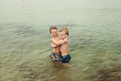 Caucasian boys hugging in lake - p555m1415935 by King Lawrence