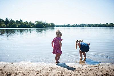 Two girls playing by lake - p924m836530f by Hugh Whitaker