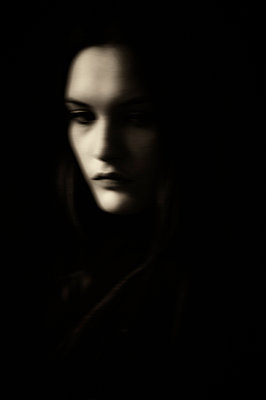 Blurred woman's face surrounded by darkness - p1047m1159911 by Sally Mundy