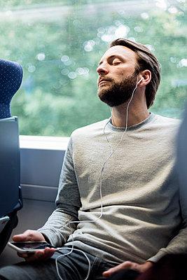 Mann hört Musik im Zug - p1114m1159731 von Carina Wendland