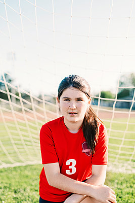 Portrait of confident girl wearing red soccer uniform against goal post during sunny day - p1166m2060439 by Cavan Images