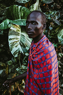 Maasai Man in traditional clothes standing in front of green leaves - p1166m2157026 by Cavan Images