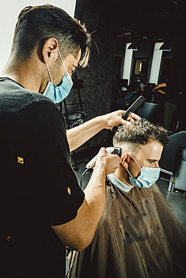 beautician and hairdresser working with mask for the covid19 virus - p1166m2200256 by Cavan Images