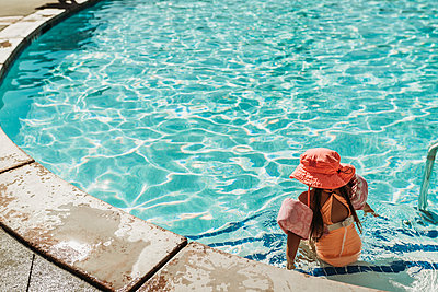 Behind view of little girl swimming in pool on vacation Palm Springs - p1166m2218173 by Cavan Images