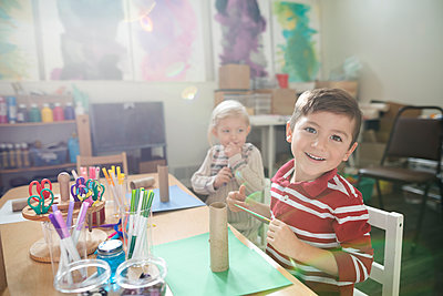 Portrait smiling boy making art and craft project in classroom - p1192m1560104 by Hero Images
