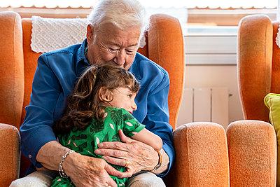 Grandmother hugging her granddaughter in living room - p300m2140382 by Gemma Ferrando