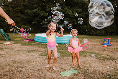 Two happy girls playing with soap bubbles in garden - p300m2206989 by Sara Monika