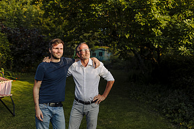 Son with father looking away while standing in back yard - p300m2276972 by Gustafsson