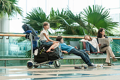 Family waiting in airport terminal - p623m659415f by Thierry Foulon