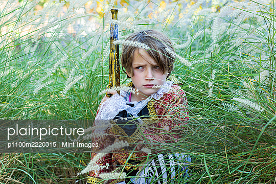 Young boy dressed as a pirate holding long pistol. - p1100m2220315 by Mint Images