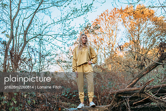 Blonde woman with curly hair and a yellow tracksuit - p1628m2260814 by Lorraine Fitch