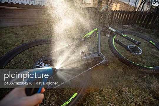 Washing a dirty mountain bike with a water hose - p1687m2284276 by Katja Kircher