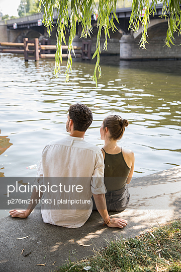 Young couple is resting by the water - p276m2111063 by plainpicture