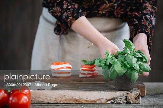 Woman preparing Caprese Salad, partial view - p300m2012397 von Alberto Bogo