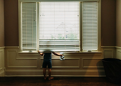 Rear view of boy with toy looking through window - p1166m1182737 by Cavan Images