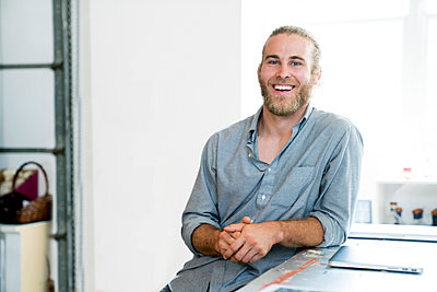 Portrait of happy businessman sitting in office - p1166m1473965 by Cavan Images