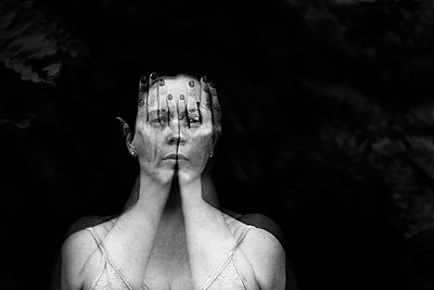 Double exposure portrait of a female behind hands - p1166m2129863 by Cavan Images