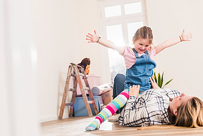 Happy mother and daughter playing in new home - p300m1459883 by Uwe Umstätter