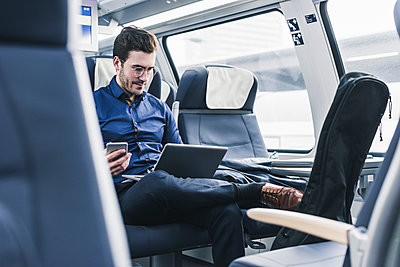 Businessman working in train using laptop - p300m1562854 by Uwe Umstätter