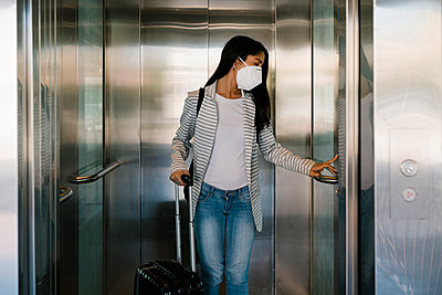 Woman wearing protective face mask pressing elevator button at station - p300m2240319 by Ezequiel Giménez