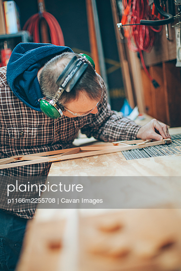 A Caucasian, middle aged man works on a small piece of a wooden airplane in his garage. - p1166m2255708 by Cavan Images