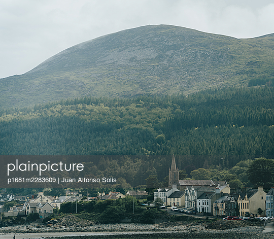 View of Newcastle against forest landscape, Northern Ireland - p1681m2283609 by Juan Alfonso Solis