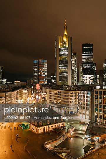 Germany, Hesse, Frankfurt, Illuminated town square at night with downtown skyscrapers in background - p300m2188107 by Hernandez and Sorokina