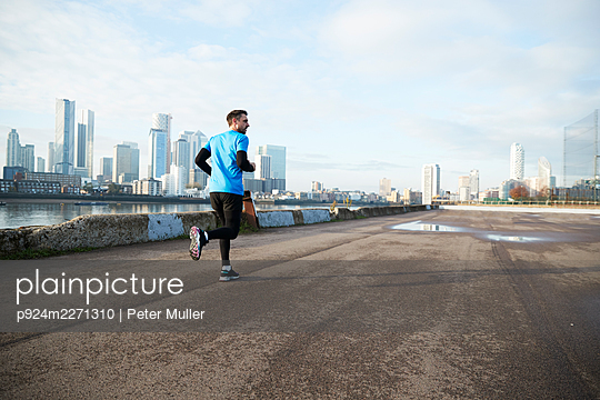 UK, London, Jogger running with downtown skyline in background - p924m2271310 by Peter Muller