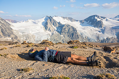 Hiker lying on mountain summit, exhausted after a long day - p1166m2153420 by Cavan Images