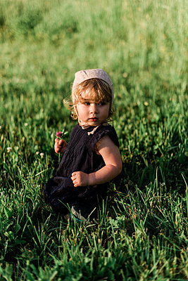 One year old girl picking wildflowers in a meadow. - p1166m2163030 by Cavan Images