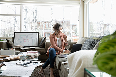 Senior female interior designer working from home, using laptop and smart phone on living room sofa - p1192m2088249 by Hero Images