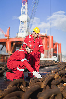Workers on oil rig examining chains - p42915021f by Hybrid Images