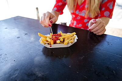 Junge Frau isst Pommes mit Ketchup - p432m1586233 von mia takahara