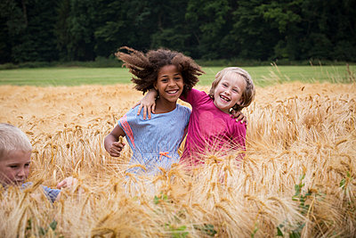 Kinder spielen auf Feld mit Gerste - p471m2022073 von CLMasur