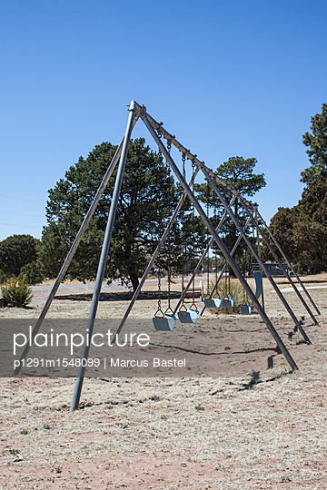 metal swings old school, on dried grass with a backdrop of trees - p1291m1548099 by Marcus Bastel