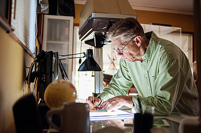 Senior man working on graphics tablet at home - p1166m1163152 by Cavan Images