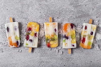 Homemade fruits and yogurt ice lollies on marble - p300m1581587 von Retales Botijero