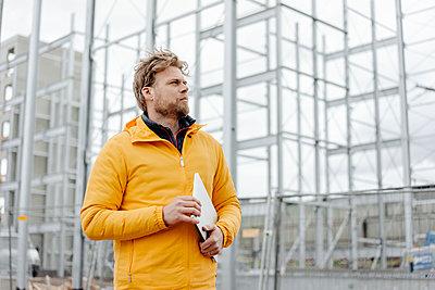 Man holding laptop, construction site in the background - p300m2005536 von Kniel Synnatzschke