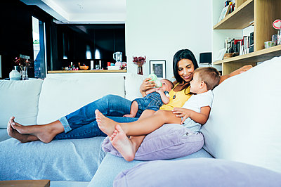 Mom with her two sons sitting on a sofa - p300m2132322 by Oscar Carrascosa Martinez
