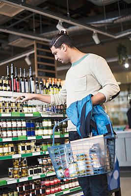Man buying groceries at supermarket - p426m1407385 by Kentaroo Tryman