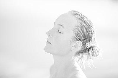 Porträt einer jungen Frau mit nassen Haaren, Profilansicht - p552m2194528 von Leander Hopf