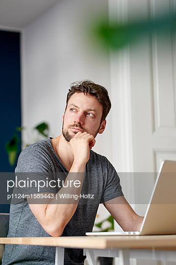 Junger Mann am Laptop zuhause - p1124m1589443 von Willing-Holtz