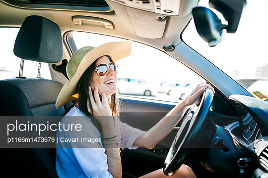 Side view of happy young woman talking on phone while sitting in car - p1166m1473679 by Cavan Images