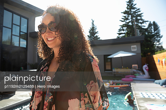 Smiling, carefree woman at sunny, summer poolside - p1192m2129488 by Hero Images