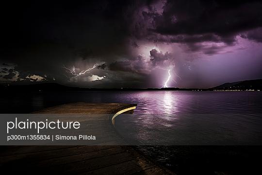 Italy, thunderstorm at a lake at night